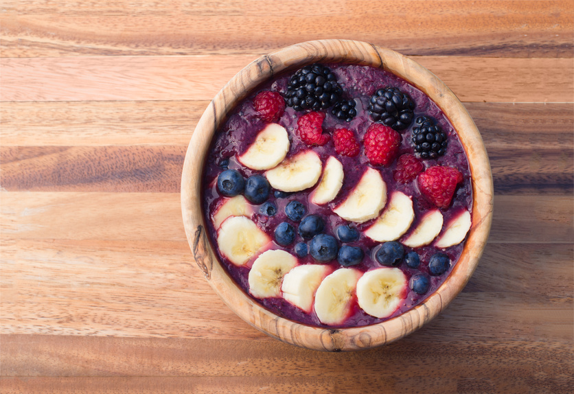 acai berry smoothie in a wooden bowl topped with bananas, blueberries, raspberries and blackberries